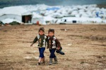 Syrian boys, whose family fled their home in Idlib, walk to their tent, at a camp for displaced Syrians, in the village of Atmeh, Syria, Monday, Dec. 10, 2012